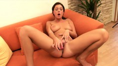 Leggy brunette cutie fucks herself with a pink dildo on the couch