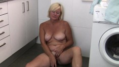 Horny grandma Sabine sits on the floor and satisfies her sexual urges