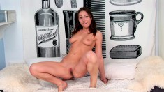 Insatiable brunette peels off her clothes and fucks herself on the bed